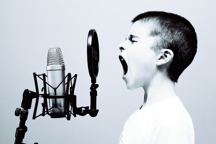 boy singing in to microphone